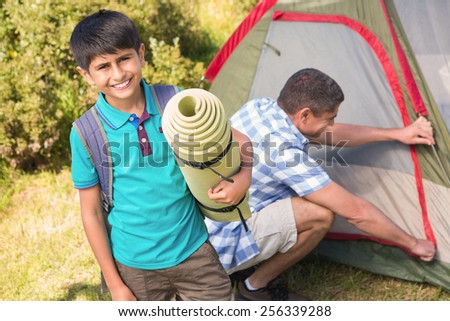 Father and son pitching their tent on a sunny day - stock photo