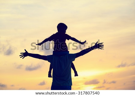 father and son play on sunset beach - stock photo