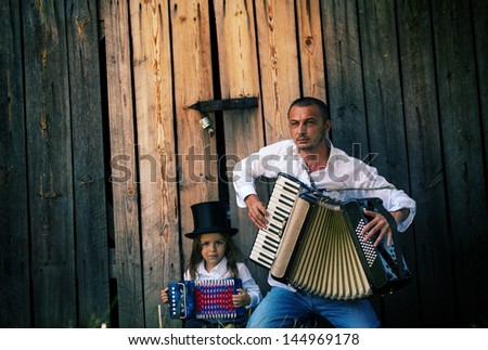 father and son playing accordion - stock photo