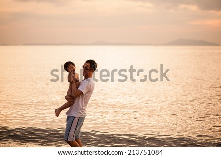 Father and son playing at beach - stock photo