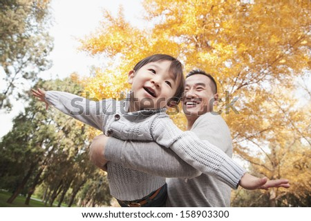 Father and son playing at park in autumn - stock photo
