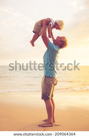 Father and son playing at sunset - stock photo