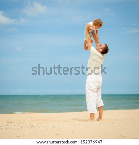 father and son playing at the beach in the day time