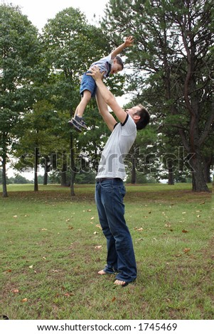 Father and son playing at the park. - stock photo