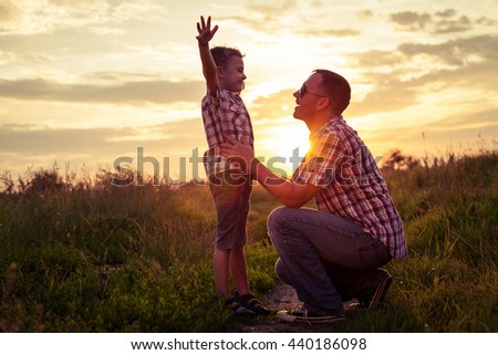 Father and son playing at the park at the sunset time. People having fun on the field. Concept of friendship forever and of summer vacation. - stock photo