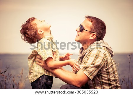 Father and son playing at the park near lake at the day time. Concept of friendly family. - stock photo