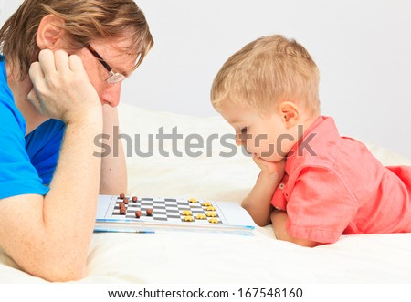 father and son playing checkers, early education and family concept - stock photo