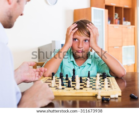 Father and son playing chess at home, boy losing - stock photo