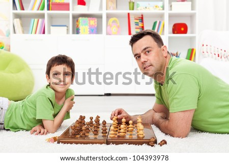 Father and son playing chess - family spending time together