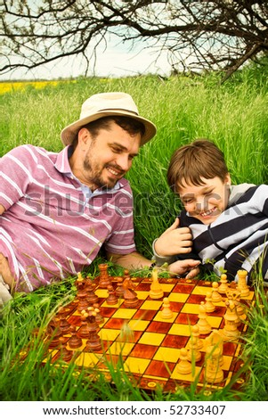 Father and son playing chess outdoors - stock photo