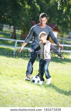 Father and son playing football - stock photo