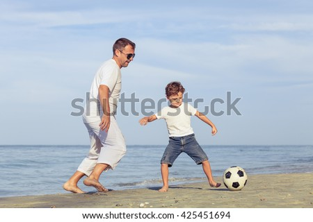 Father and son playing football on the beach at the day time. Concept of friendly family. - stock photo