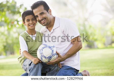 Father and son playing football together - stock photo