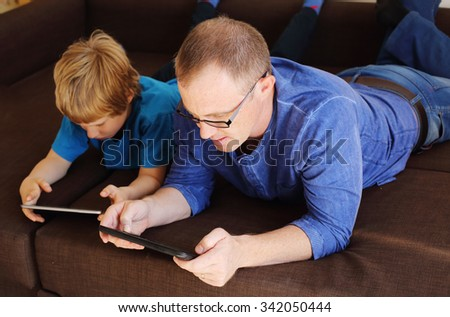 father and son playing games on tablets