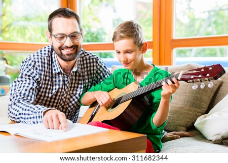 Father and son playing guitar at home, making music together - stock photo