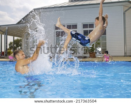 Father and son playing in pool - stock photo