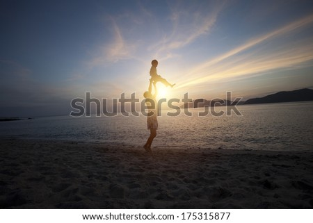 father and son playing in sunset on beach
