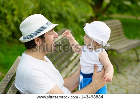 Father and son playing in the park and sitting on the bench - stock photo