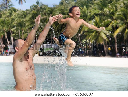 father and son playing in water