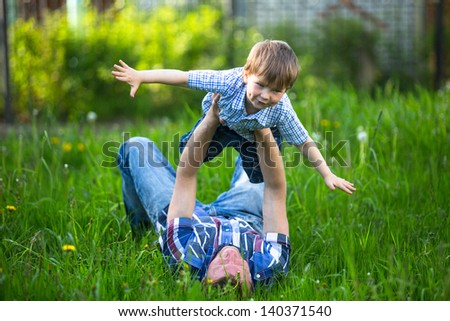 Father and son playing lying on the grass in the park - stock photo