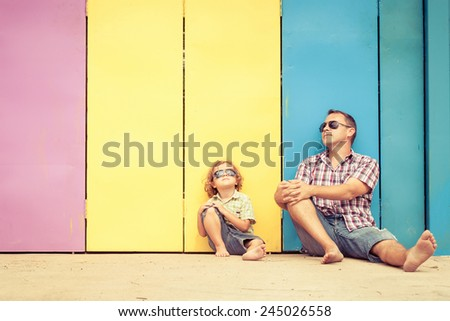 Father and son playing near the house at the day time. They sitting near are the colorful wall. Concept of friendly family. - stock photo