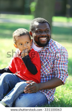 Father and son playing on grass in the park