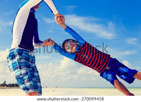 father and son playing on summer beach - stock photo