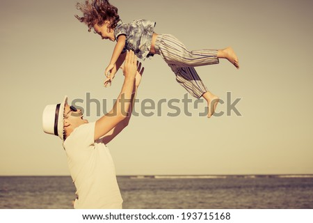 father and son playing on the beach at the day time - stock photo