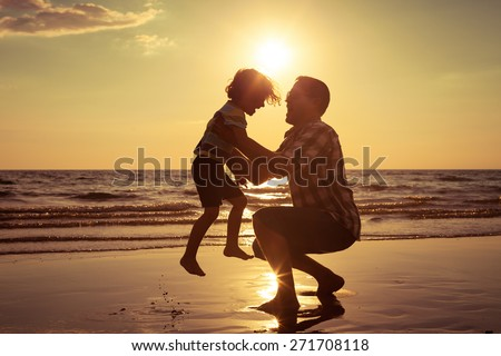 Father and son playing on the beach at the sunset time. Concept of friendly family. - stock photo