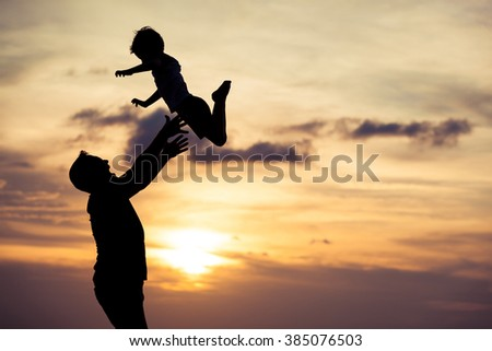 Father and son playing on the beach at the sunset time. Concept of happy friendly family.