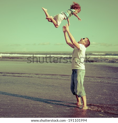 father and son playing on the beach in the day time - stock photo