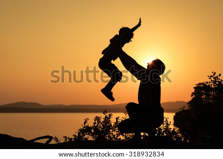 father and son playing on the coast of lake in the mountains of at the sunset time
