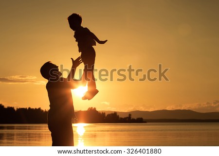 Father and son playing on the coast of lake in the mountains of at the sunset time.  Concept of friendly family. - stock photo
