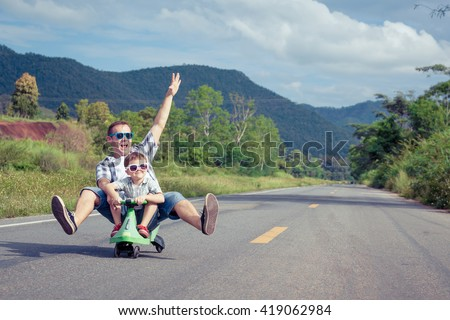 Father and son playing  on the road at the day time.  Concept of friendly family. - stock photo