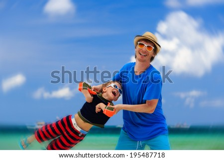 father and son playing on tropical beach - stock photo