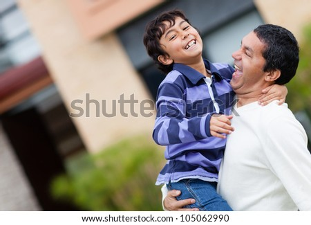 Father and son playing outdoors and looking very happy - stock photo