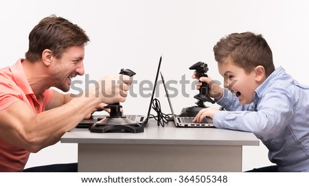 Father and son playing the computer games - stock photo