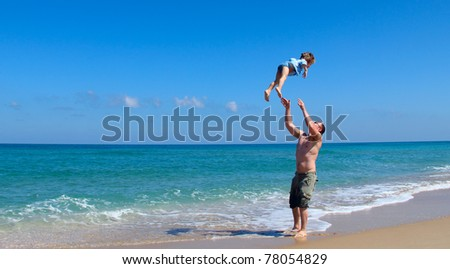 father and son playing together on the beach - stock photo