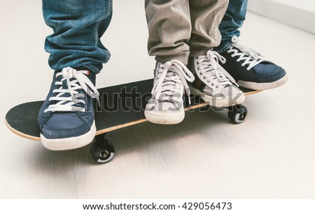 Father and son playing together on the skateboard. Teaching balance and playing together at home