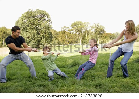 Father and son playing tug of war with mother and daughter. - stock photo