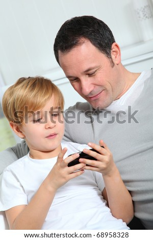 Father and son playing video game at home - stock photo