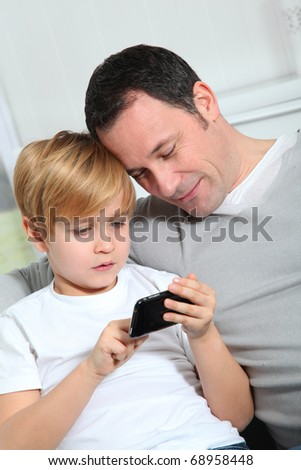 Father and son playing video game at home