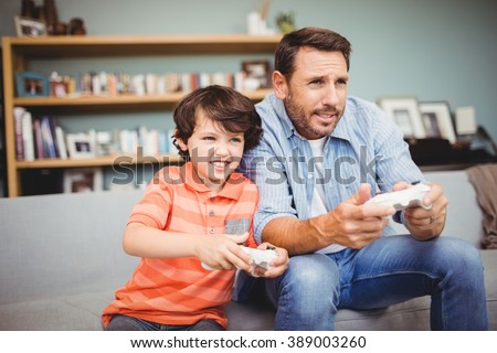 Father and son playing video game while sitting on sofa at home - stock photo