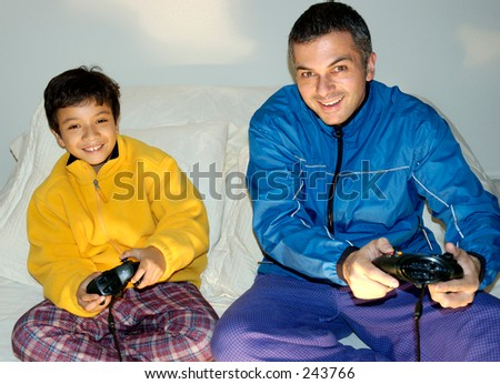 Father and son playing video games. - stock photo
