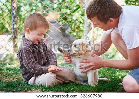 father and son playing with a puppy Labrador. - stock photo