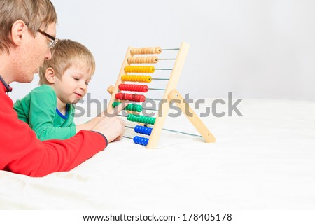 father and son playing with abacus, early education - stock photo