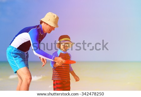 Father and son playing with flying disc at tropical beach - stock photo