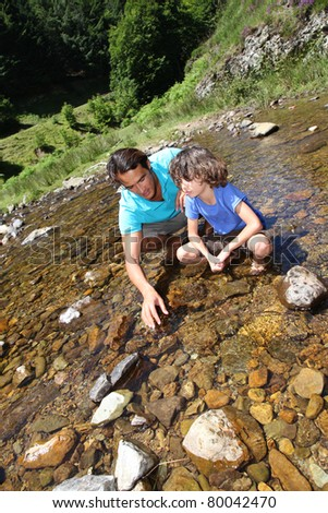 Father and son playing with peebles in river - stock photo