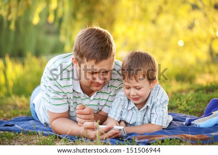 Father and son playing with smartphone  together outdoors - stock photo