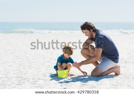 Father and son playing with toys at beach. Family of father and son enjoying summer vacation at beach. Father helping son fill basket with sand. - stock photo